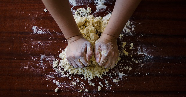 hands kneading dough on worksurface